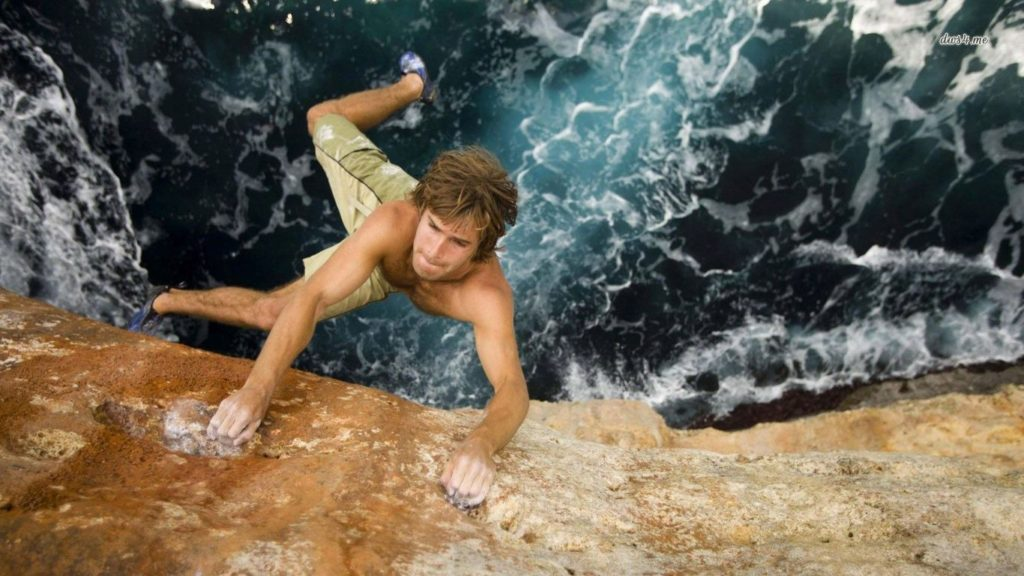 Rock climber free solos above water